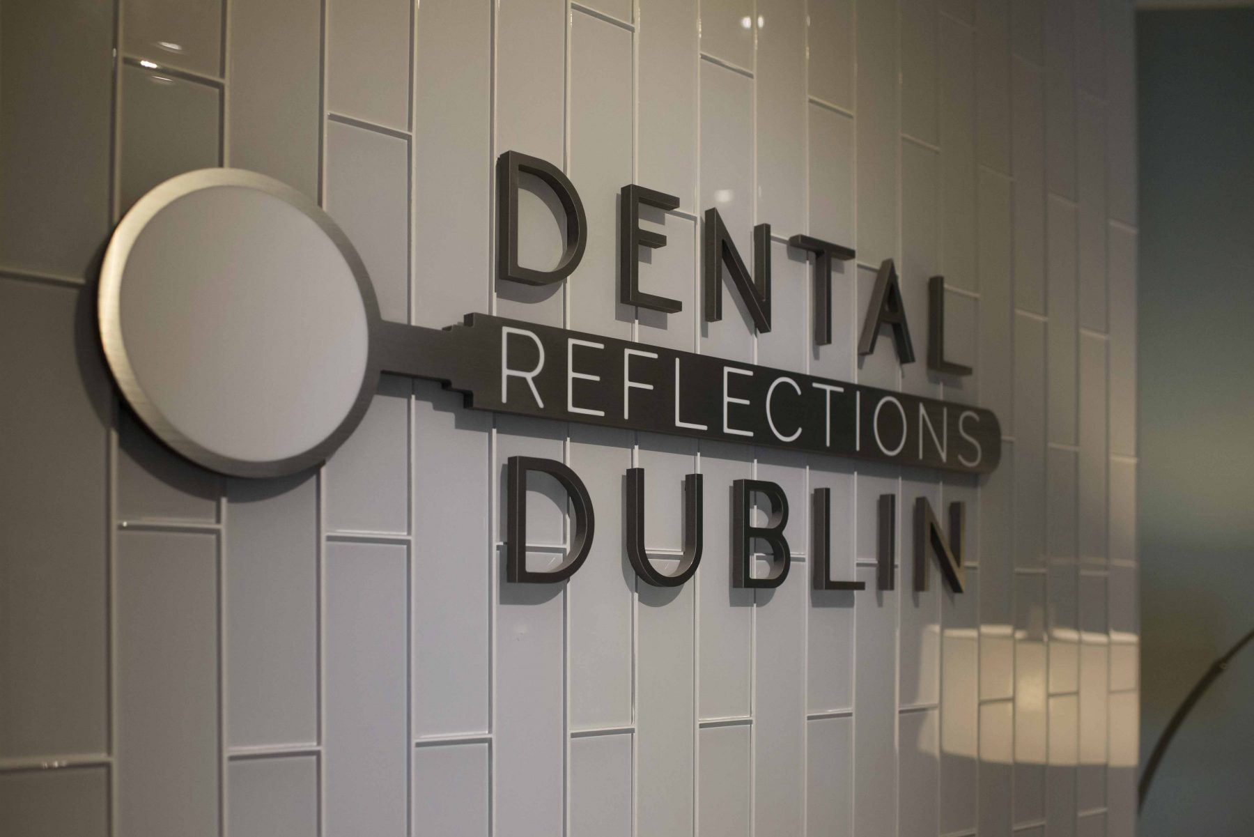 gray wall of tiles with Dental Reflections Dublin logo on it