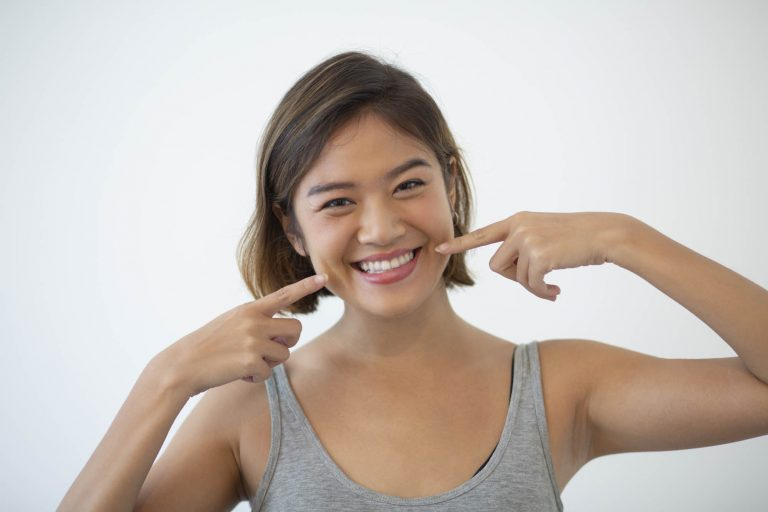 Smiling woman pointing at her white teeth
