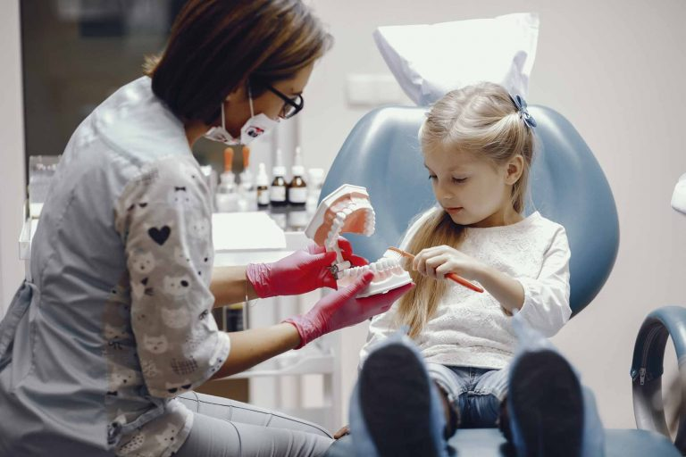 child sitting in dental chair brushing a tooth model held by a dental hygienist