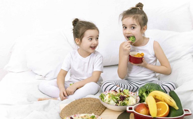 kids eating healthy food while sitting on a bed