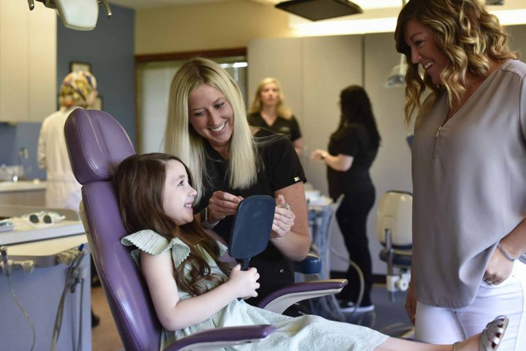 a smiling child sits in a dental chair holding a mirror while two female employees smile at her
