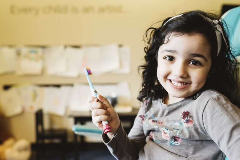 portrait of a child holding a toothbrush while smiling at the camera