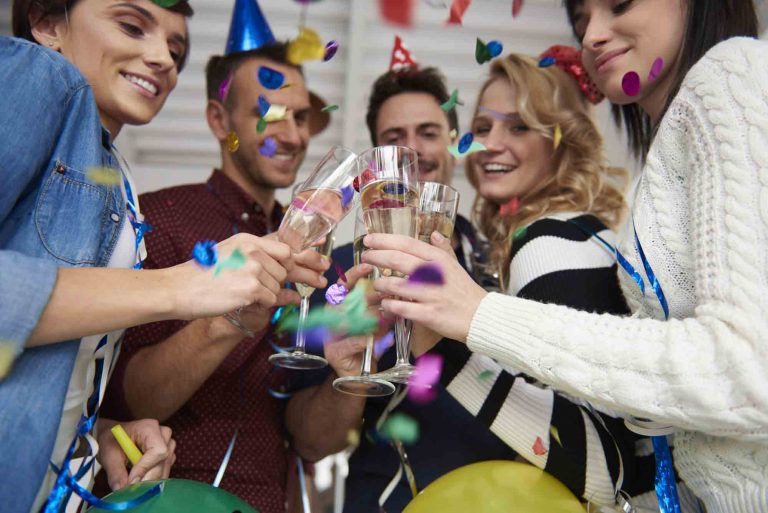 a group of people toasting their glasses together while confetti falls over them