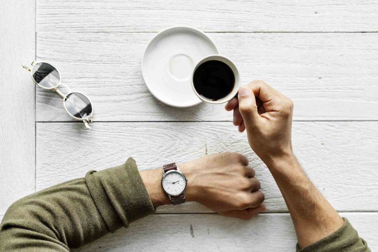 one arm with watch on it rests on a white wood table next to a pair of sunglasses while the other arm holds a cup of coffee