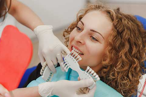 female sites in a dental chair while the dentist compares which shade of tooth color matches the patient's teeth